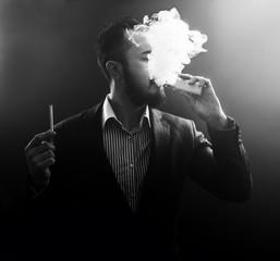 vaping man holding a mod and cigarette. A cloud of vapor.
