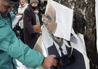 Civic activists  pelt shoes on a poster of Sulejman Tihic in Sarajevo