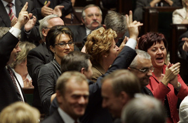 Members of parliament react after voting to shorten its term and pave the way for a snap poll in Warsaw
