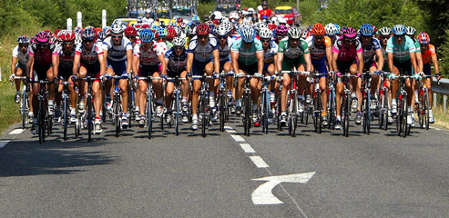 RIDERS MAKE THEIR WAY ALONG A TWO LANE ROAD DURING SIXTH STAGE OF TOURDE FRANCE.