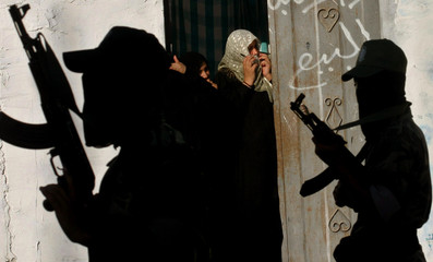 Palestinian women watch militants march during a rally in Rafah camp at the southern Gaza Strip.