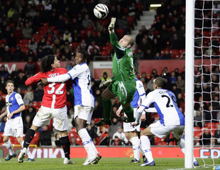 Blackburn Rovers' goalkeeper Robinson saves header from Manchester United's Tevez during their English League Cup soccer match
