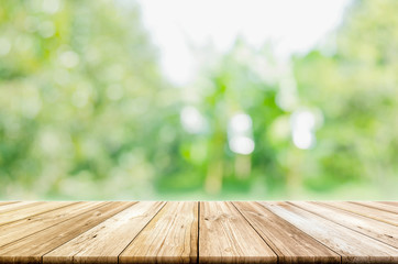 Empty wooden table top with blurred green natural background.