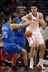 Orlando Magic guard Hedo Turkoglo (L) and Houston Rockets center Yao Ming (R) battle over a loose ball.