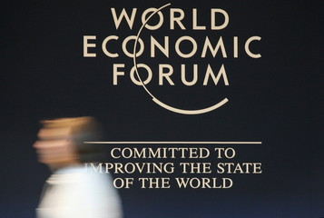 A woman walks by a WEF logo inside the Congress Centre, venue of the World Economic Forum (WEF) in D..