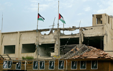 Palestinian flags downed over damaged headquarters of President Yasser Arafat in Gaza.