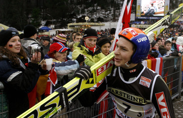 Norway's Jacobsen walks past spectators during the men's team ski jumping World Cup competition in the town of Willingen