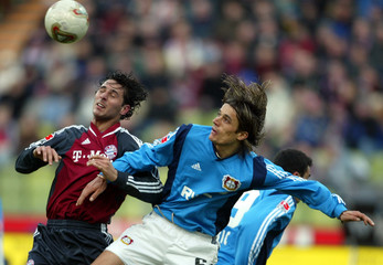 ZIVKOVIC OF BAYER 04 LEVERKUSEN HEADS THE BALL WITH FC BAYERN MUNICH'SPIZARRO.