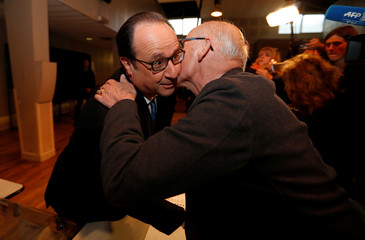 French President Francois Hollande is greeted by a supporter after voting in the second round of 2017 French presidential election at a polling station in Tulle