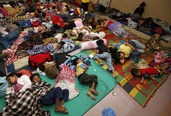 People sleep in a temporary shelter after fleeing their damaged homes shocked by a powerful earthquake in Padang