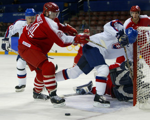 AUSTRIAN LANZINGER CROSS CHECKS SLOVAKIAN PARDAVY INTO POST IN MENS ICEHOCKEY ACTION.