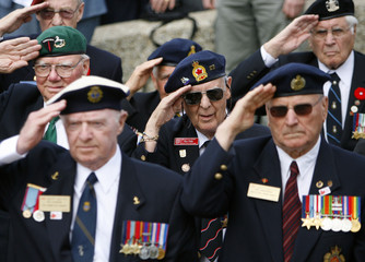 Retired Major Eddy salutes with other Canadian WW2 veterans at a Royal Regiment of Canada memorial in Puys