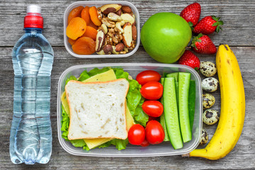 Healthy lunch boxes with sandwich, eggs and fresh vegetables, bottle of water, nuts and fruits