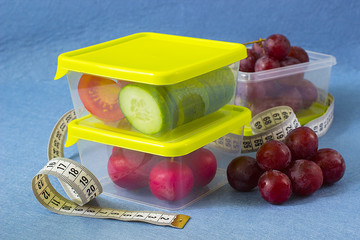 A plastic food containers with fresh vegetables and fruits and centimeter tape.