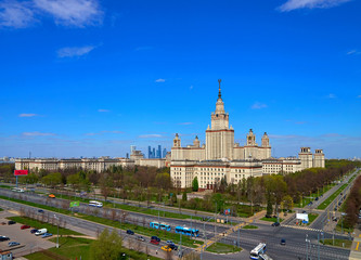A landscape view of the sunny spring campus of Lomonosov Moscow State University under blue cloudy sky