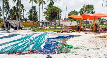 large colorful fishing nets on african sandy beach with village on the background