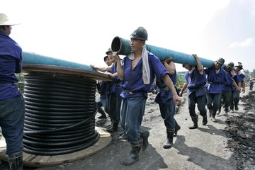 Rescuers carry pipes to drain out water from a flooded coal mine in Xintai