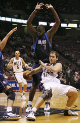 New Jersey Nets Kristic loses ball as he falls in front of Dallas Mavericks Diop in their NBA basketball game in East Rutherford