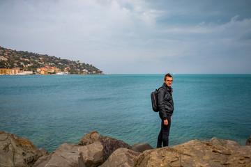 Jeune homme sur la digue du port de Porto Santo Stefano en Toscane