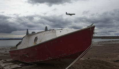 A First Air 737 commercial jet comes into land at the local airport as a boat sits high from the receding tide in Iqaluit