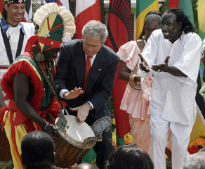 U.S. President Bush plays the drums with Senegalese dancers at the White House in Washington