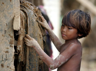 A Filipino boy collects mud soaked clothes in a typhoon devastated village in Infanta town in Quezon..