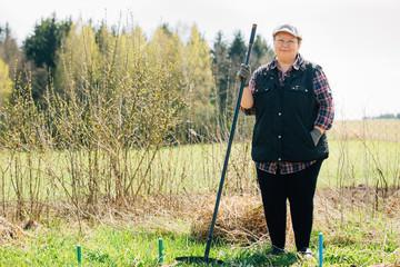 Mature woman raking garden. Senior woman with rake spring cleaning