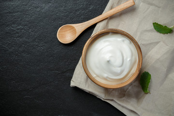 Greek yogurt in a wooden bowl with spoons on stone background