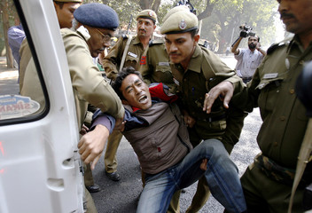 Police detain a Tibetan exile outside the venue of the India-China joint meeting in New Delhi
