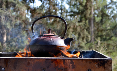 Old iron cast teapot kettle on campfire