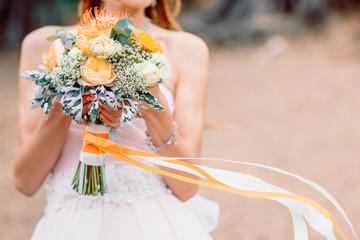 Beautiful wedding bouquet in hands of bride.