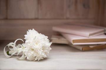 A white bouquet of flowers lies on a wooden table. Background or frame