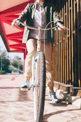 Woman on a bicycle in a green shirt and beige pants in the city
