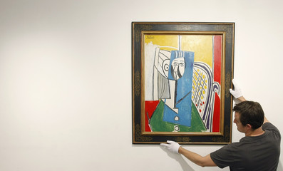 Display coordinator Sheppard hangs a painting by Pablo Picasso at an auctioneers in Sydney