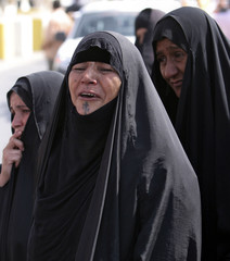 Women mourn during a funeral for the 30 bodies that were unearthed in Basra