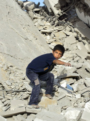 PALESTINIAN BOY WALKS ON RUBBLE OF THREE BUILDINGS DESTROYED BY ISRAELIARMY IN GAZA STRIP.