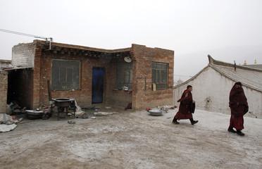 Tibetan monks walk from their home towards a prayer meeting at a monastery near Tongren