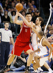 Houston Rockets center Yao Ming looks to pass over Oklahoma City Thunder defenders during their NBA basketball game in Oklahoma