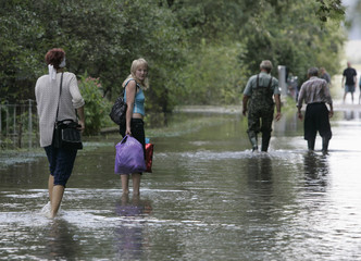 People walk on a flooded road in a settlement near the city of Galych in the Ivano-Frankivsk