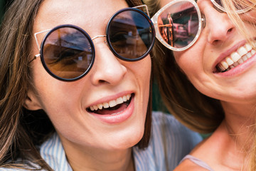 two beautiful girls smile, happy girls, white teeth, beautiful smiles. Two beautiful happy girls in sunglasses on the urban background. Young active people. Outdoors
