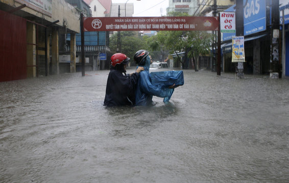A couple carries a computer through a flooded street in Hanoi