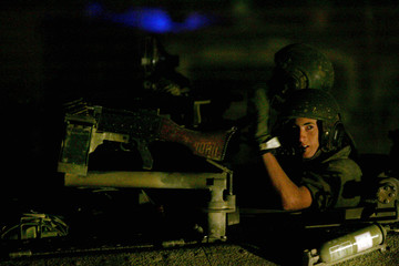 An Israeli soldier gestures as he drives his tank out of the Gaza Strip at the Kisufim crossing.