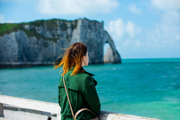 young woman on cliffs and sea background, Etretat, France