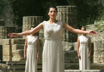 GREEK ACTRESS RAISES HER ARMS DURING A CEREMONY IN ANCIENT OLYMPIA.