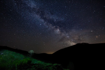 Starry sky with Milky way and silhouette of mountains, green grass and bushes on foreground