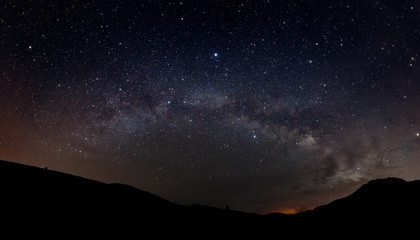 Starry sky with Milky way and silhouette of mountains