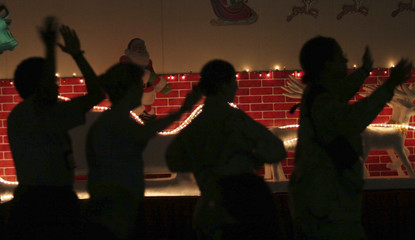 US soldiers are silhouetted as they dance during a new year celebration at the IZ hospital in Baghdad