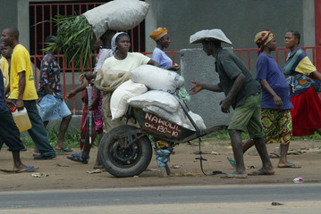 LIBERIAN'S CARRY SACKS OF FOOD AFTER STORMING INTO MONROVIA'S PORT.