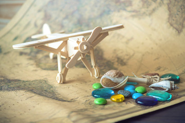Toy wooden plane on a world map with colored stones and shells from the sea in a retro style.