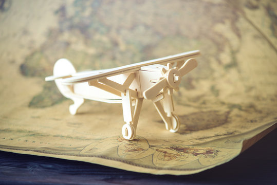 Wooden toy airplane flies on world map background in retro style